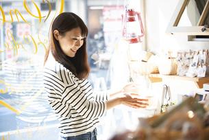 雑貨屋で商品を選んでいる女性の写真素材 [FYI04315430]