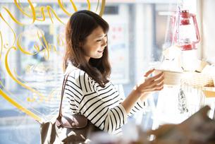 雑貨屋で商品を選んでいる女性の写真素材 [FYI04315431]