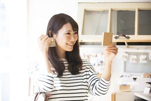 雑貨屋でアクセサリーを選んでいる女性の写真素材 [FYI04315437]