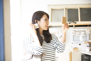 雑貨屋でアクセサリーを選んでいる女性の写真素材 [FYI04315438]