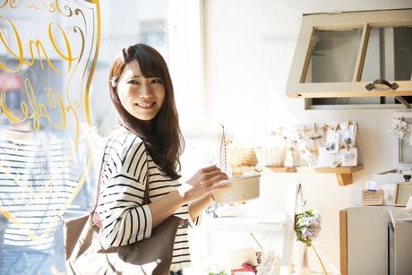 雑貨屋でアクセサリーを選んでいる女性の写真素材 [FYI04315440]