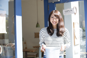 お店の前で笑っている女性の写真素材 [FYI04315442]