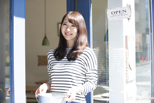 お店の前で笑っている女性の写真素材 [FYI04315443]