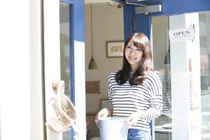 お店の前で笑っている女性の写真素材 [FYI04315444]