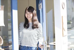 お店の前で笑っている女性の写真素材 [FYI04315445]