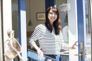お店の前で看板を持って笑っている女性の写真素材 [FYI04315446]