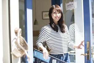 お店の前で看板を持って笑っている女性の写真素材 [FYI04315447]