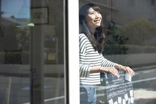 お店の中で看板を持って笑っている女性の写真素材 [FYI04315448]