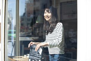 お店の中で看板を持って笑っている女性の写真素材 [FYI04315449]