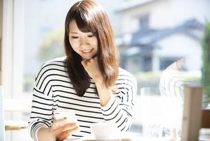 カフェでスマホを見ている女性の写真素材 [FYI04315451]