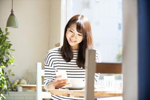 カフェでスマホを見ている女性の写真素材 [FYI04315453]