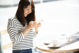 カフェでスマホを使って撮影をしている女性の写真素材 [FYI04315454]