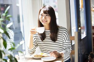カフェでコーヒーカップを持っている女性の写真素材 [FYI04315456]