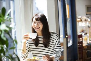 カフェでコーヒーカップを持っている女性の写真素材 [FYI04315457]