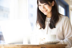 カフェでパソコンを使って仕事をしている女性の写真素材 [FYI04315459]