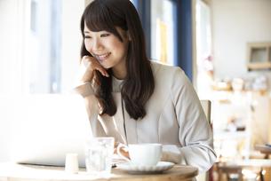 カフェでパソコンを使って仕事をしている女性の写真素材 [FYI04315461]