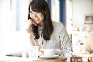 カフェでパソコンを使って仕事をしている女性の写真素材 [FYI04315463]