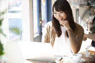 カフェでパソコンを使って仕事をしている女性の写真素材 [FYI04315465]