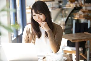 カフェでパソコンを使って仕事をしている女性の写真素材 [FYI04315466]