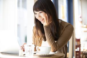 カフェでパソコンを使って仕事をしている女性の写真素材 [FYI04315468]