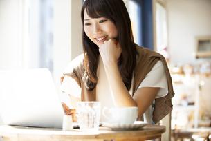 カフェでパソコンを使って仕事をしている女性の写真素材 [FYI04315469]