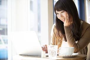 カフェでパソコンを使って仕事をしている女性の写真素材 [FYI04315470]