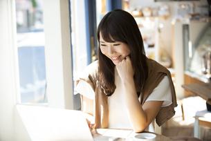 カフェでパソコンを使って仕事をしている女性の写真素材 [FYI04315471]