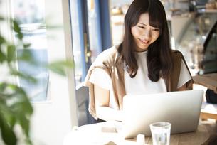 カフェでパソコンを使って仕事をしている女性の写真素材 [FYI04315473]