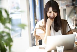 カフェでパソコンを使って仕事をしている女性の写真素材 [FYI04315475]