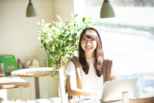 カフェでパソコンを使って仕事をしている女性の写真素材 [FYI04315482]