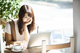 カフェでパソコンを使って仕事をしている女性の写真素材 [FYI04315484]