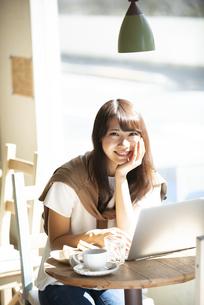 カフェでパソコンを使って仕事をしている女性の写真素材 [FYI04315485]
