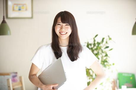 ノートパソコンを抱えて笑っている女性の写真素材 [FYI04315486]