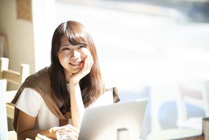 カフェでパソコンを使って仕事をしている女性の写真素材 [FYI04315487]