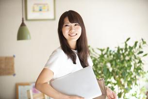 ノートパソコンを抱えて笑っている女性の写真素材 [FYI04315488]