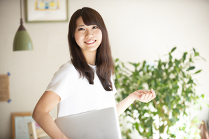 ノートパソコンを抱えて笑っている女性の写真素材 [FYI04315489]