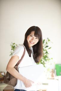 ノートパソコンを抱えて笑っている女性の写真素材 [FYI04315491]