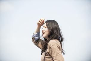 遠くを見ながら笑っている女性の写真素材 [FYI04315500]