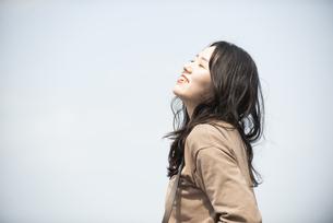 空を見上げて笑っている女性の写真素材 [FYI04315501]