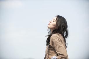 空を見上げて目を閉じている女性の写真素材 [FYI04315502]