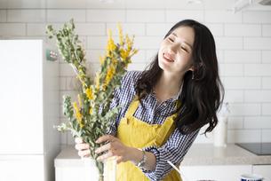 キッチンでエプロンを付けて花を飾っている女性の写真素材 [FYI04315513]