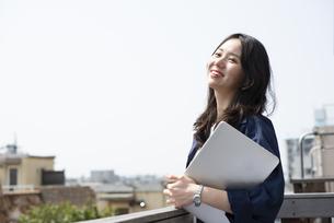 ノートパソコンを持って笑っている女性の写真素材 [FYI04315541]