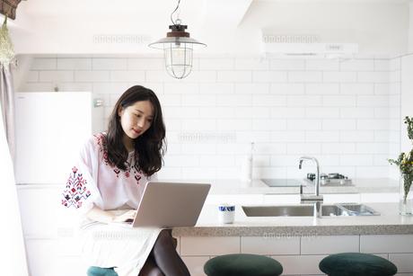 キッチンでパソコンを触っている女性の写真素材 [FYI04315553]