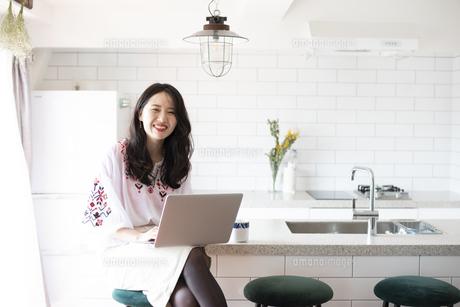 キッチンでパソコンを触っている女性の写真素材 [FYI04315556]