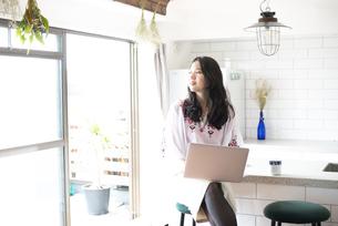 キッチンでパソコンを触っている女性の写真素材 [FYI04315561]