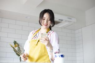 キッチンでスマホを見ている女性の写真素材 [FYI04315565]
