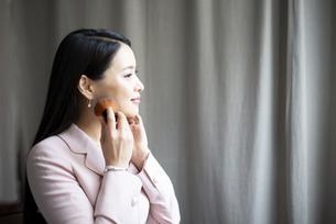 お化粧をしているスーツ姿の女性の写真素材 [FYI04315571]