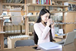 オフィスでお茶を飲んでいる女性の写真素材 [FYI04315579]