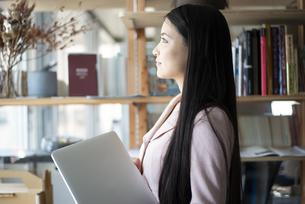 オフィスでパソコンを抱えて立っている女性の写真素材 [FYI04315588]