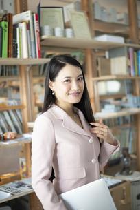 オフィスでパソコンを抱えて立っている女性の写真素材 [FYI04315590]